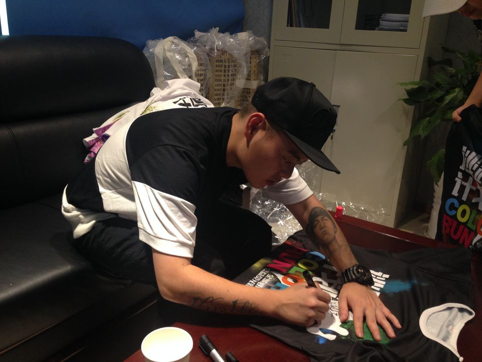 Fat Shady signs autographs backstage before a show in Luzhou.