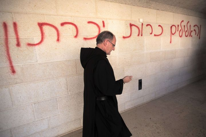 <span>A priest walks past a graffiti reading in Hebrew 'idols will be cast out' as he inspects the damage at the Church of th
