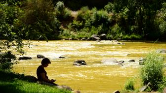 DURANGO, CO - AUGUST 8: Trisha Rickey sits near the shore of the Animas River after taking pictures of the river August 8, 2015. Over a million gallons of mine wastewater from the Gold King Mine in Silverton has made it's way into the Animas River closing the river and put the city of Durango on alert. (Photo By Brent Lewis/The Denver Post via Getty Images)