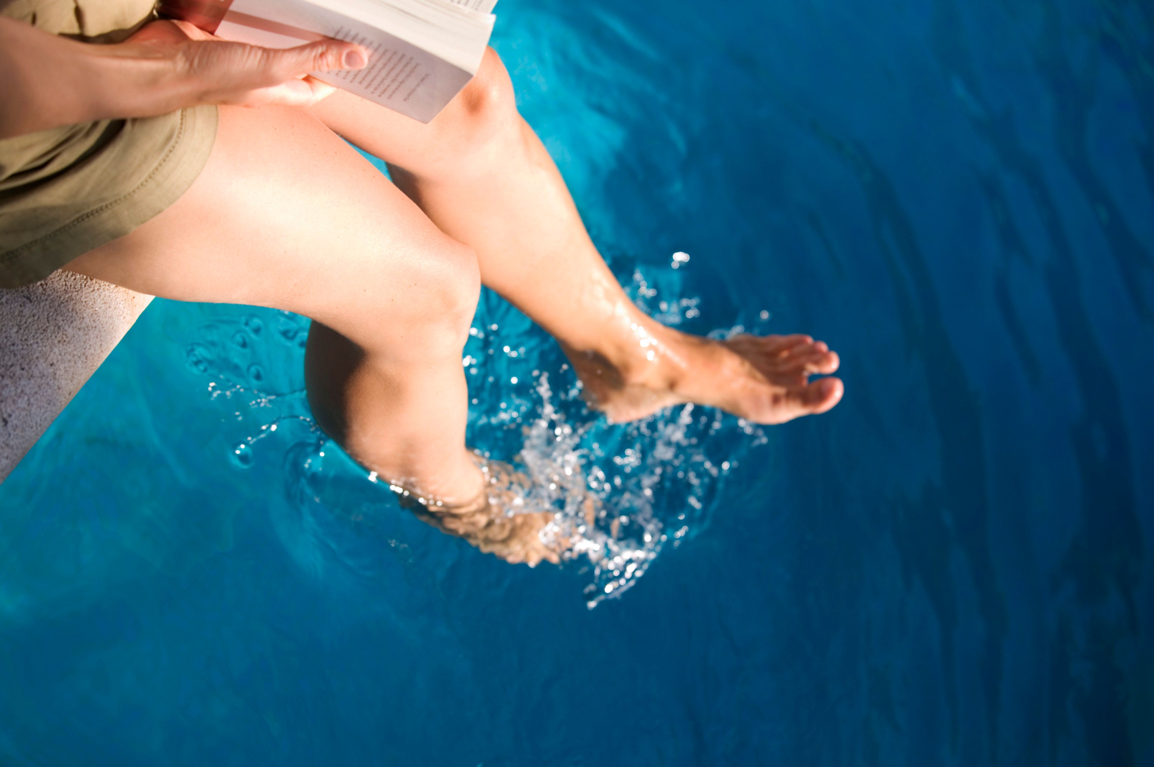 Woman sitting with feet in pool