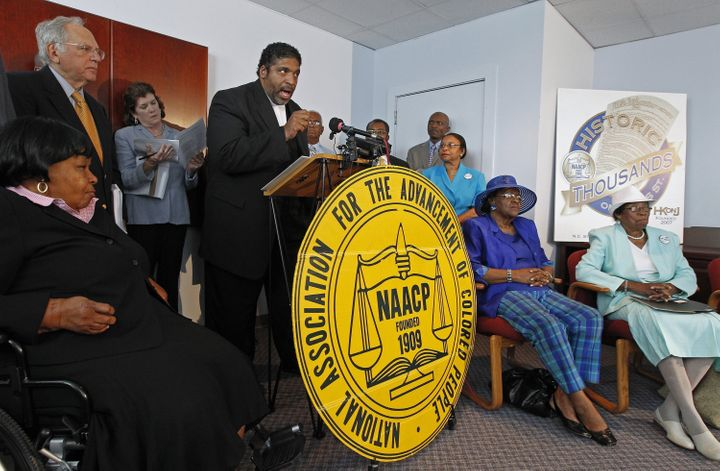<span>The Rev. William Barber, head of the N.C. NAACP, at podium, announces that the group is filing a lawsuit against the re