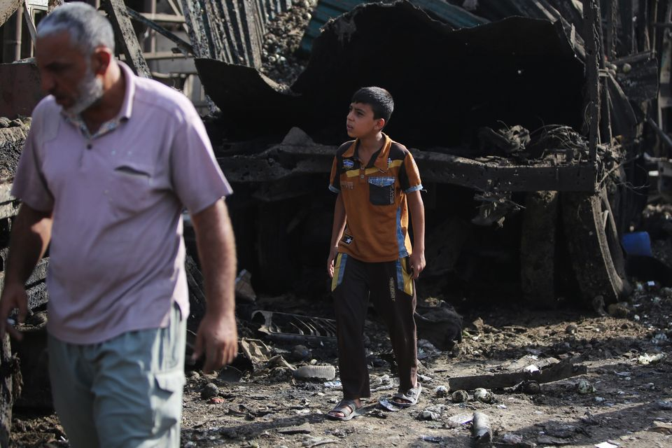 An Iraqi boy inspects the damage following a bomb attack in Baghdad, Iraq, on Aug. 13, 2015.