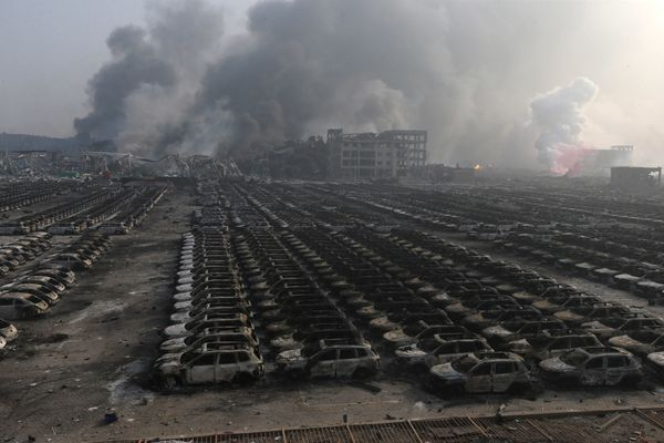 Burnt car debris continues to smolder following the explosions at a warehouse in Tianjin on Aug. 13, 2015.