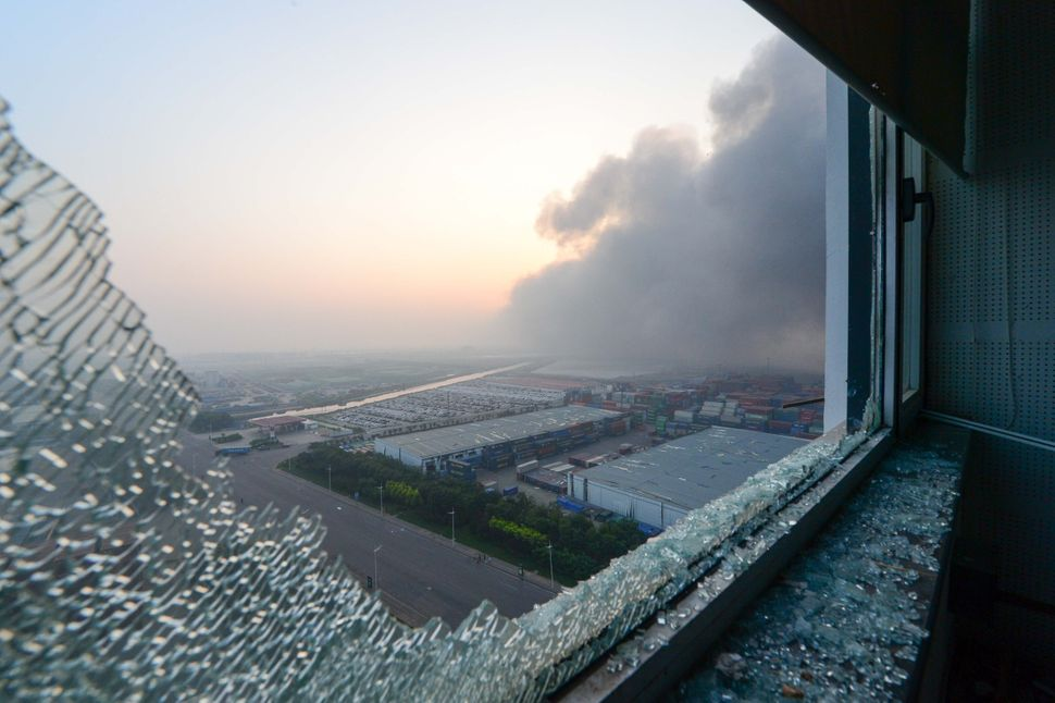 Smoke is seen out of the broken window of an apartment near the site of the explosions in Tianjin on Aug. 13, 2015.&nbsp