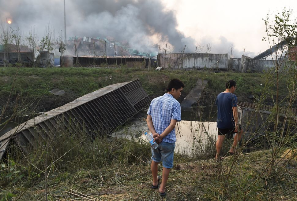 Two men walk past damaged containers at the site of an explosion in Tianjin, on Aug. 13, 2015.