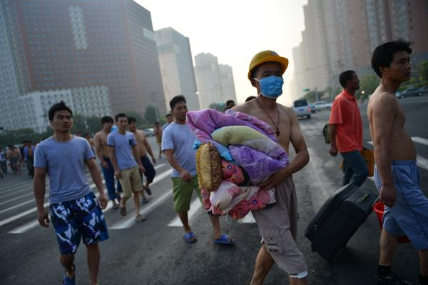 Construction workers walk near the site of massive explosions in Tianjin, Aug. 13, 2015.