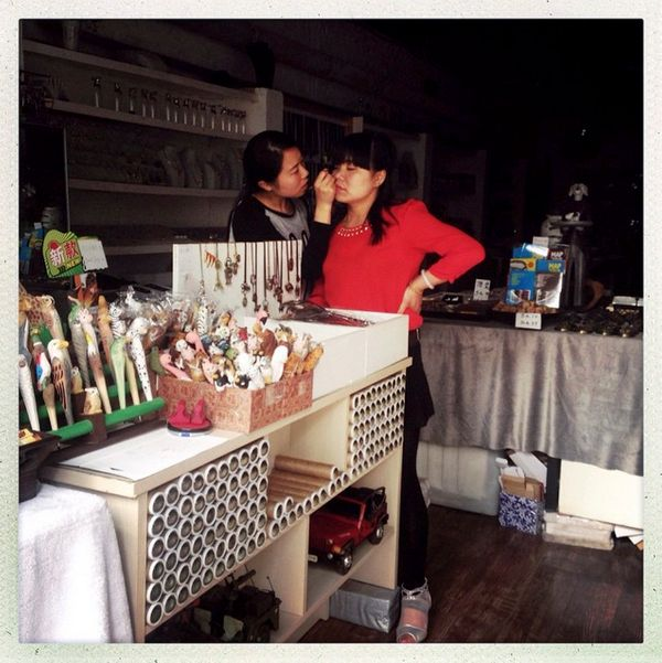 A woman gives another a private make-up session in a souvenir shop in the 798 art district in Beijing.