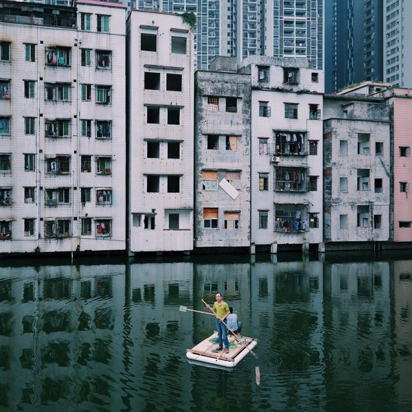 Two men fish in a pond in Xian Village in the city center of Guangzhou, China.