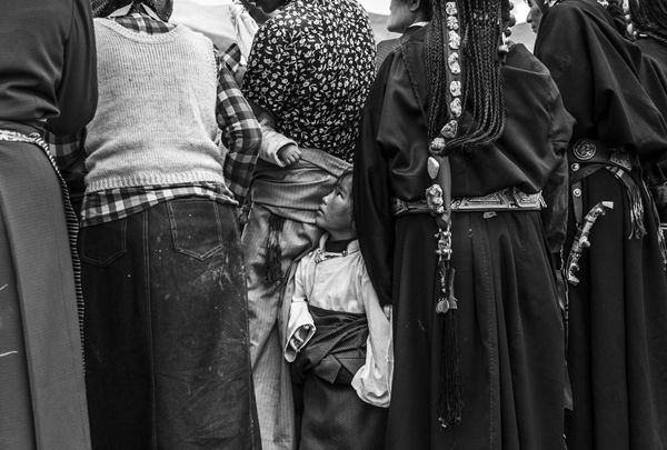A child looks up at peopleparticipating in an austere religious ceremony, blessing the new praying quarter of the Chong