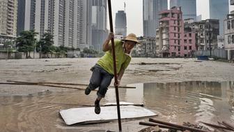 """A migrant worker does an impromptu pole vault to get over a puddle while installing cables near a half demolished """"urban village"""" in Guangzhou, southern China. Picture by @chiyin_sim /@viiphoto."""