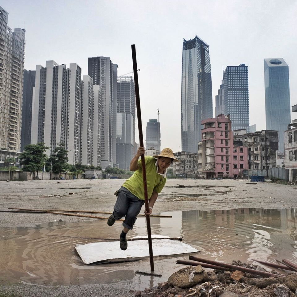 "A migrant worker pole vaults over a puddle while installing cables near a half demolished ""urban village"" in Guangzhou,"