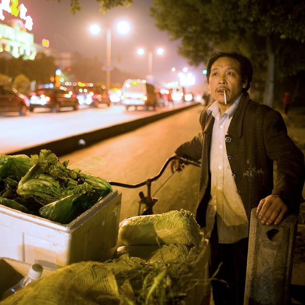 A mancollects vegetables from a night market for his fruit and vegetable stand in Shanghai.