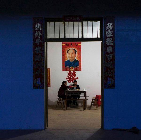 A couple eats dinner under a poster of Mao Zedong at home after a day working in the fields.