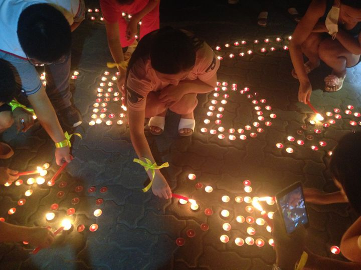 People hold a candlelight vigil for those harmed by the explosions.