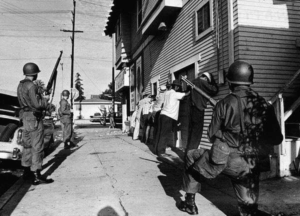 Armed National Guardsmen force a line of Black men to stand against the wall of a building during the Watts race riots, Los A
