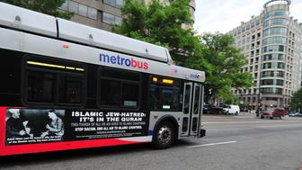 A Metro bus, featuring a controversial ad, drives on a street in Washington, DC on May 21, 2014.  Bus-ads linking 'Islamic Jew-hatred' Islam with Adolf Hitler are out on the streets of Washington, and the US capital's mass transit authority said May 20 it is legally powerless to ban them.The elongated broadsides on 20 Metro buses feature a photo of the Nazi German dictator Adolf Hitler in conversation with 'his staunch ally' Haj Amin al-Husseini, grand mufti of Jerusalem during World War II. 'Islamic Jew-hatred: It's in the Quran. Two-thirds of all US aid goes to Islamic countries. Stop racism. End all aid to Islamic countries,' the ad states, over a fine-print disclaimer from the Metro transit authority. The ads, which are to run until mid-June, were placed by the American Freedom Defense Initiative (AFDI), which aims to 'raise awareness of the depredations of Islamic supremacism,' according to its website.   AFP PHOTO / Karen BLEIER        (Photo credit should read KAREN BLEIER/AFP/Getty Images)