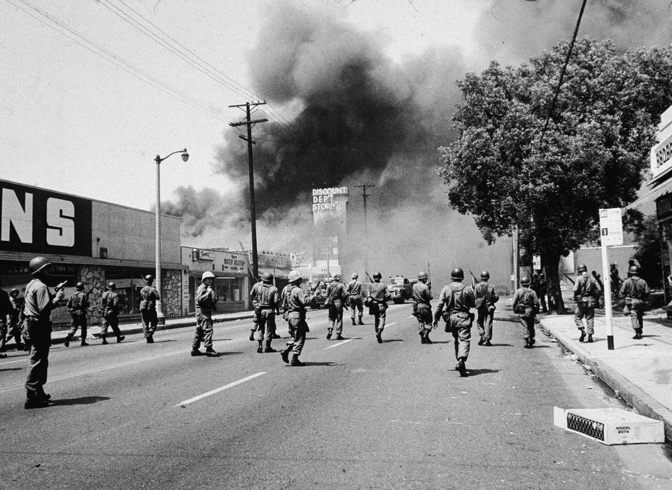 Armed National Guardsmen march toward smoke on the horizon during the street fires of the Watts riots, Los Angeles, Californi
