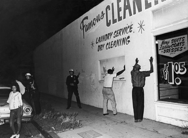 16th August 1965:  Two African-American men hold their hands up against the wall of a dry cleaners while being arrested by Ca
