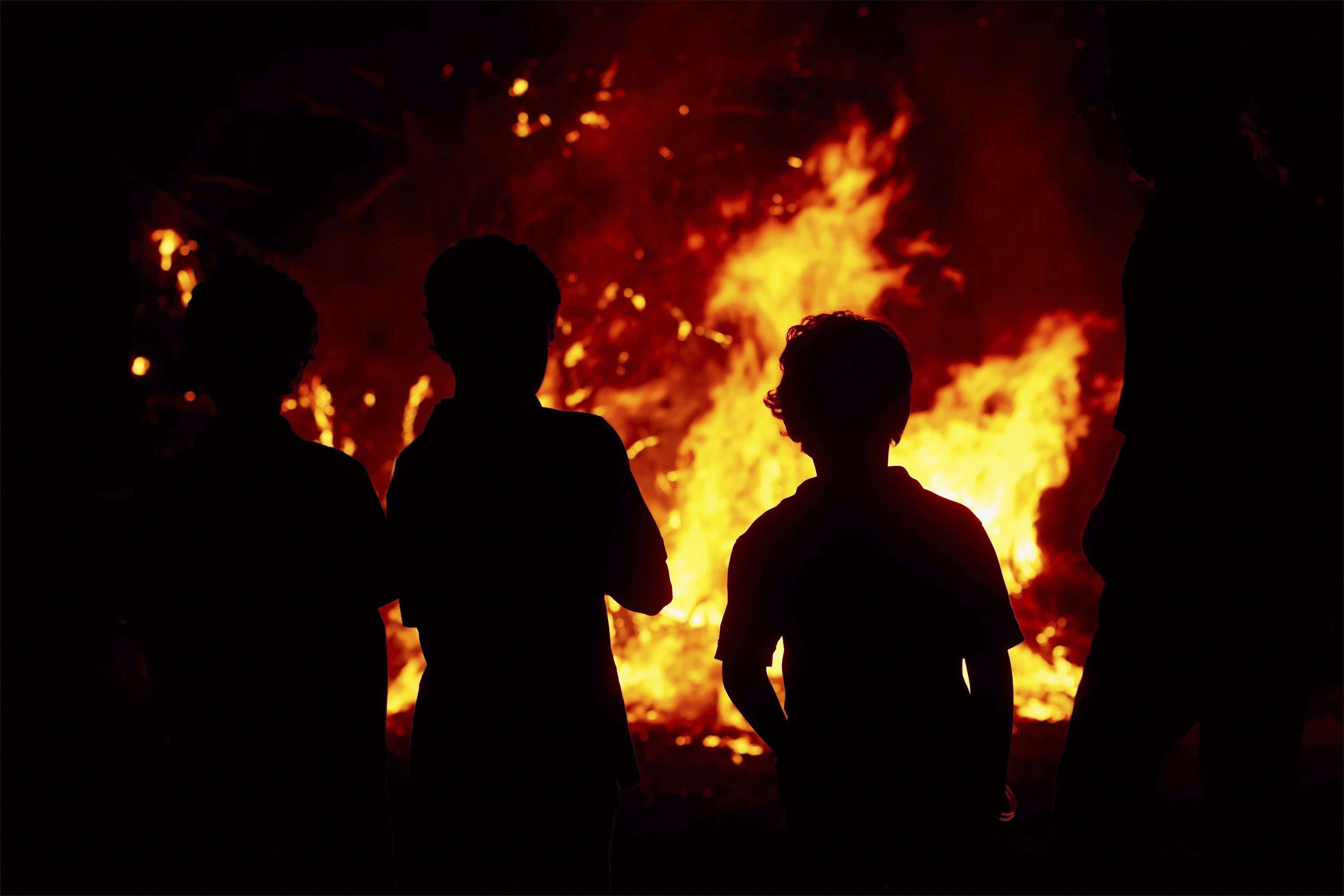 Standing around the bonfire at night.