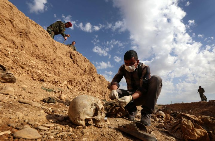 An Iraqi man inspects the remains of members of the Yazidi minority killed by the Islamic State group after Kurdish forces di