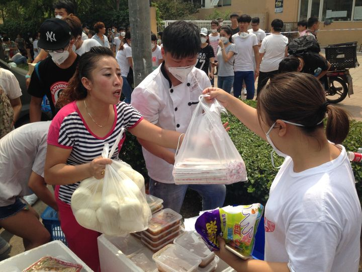 A volunteer hands out bread and chopsticks near the blast site&nbsp;<span><span>on Friday</span></span>&nbsp;afternoon.