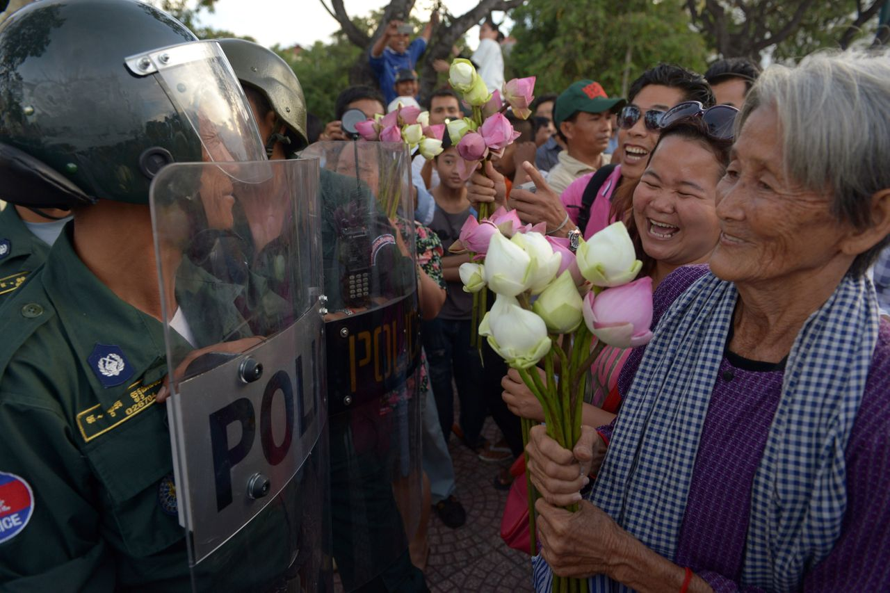 <p>Nget Khun holds lotus flowers in front of police officers during a 2013 protest against a land development project in Phnom Pehn. </p>