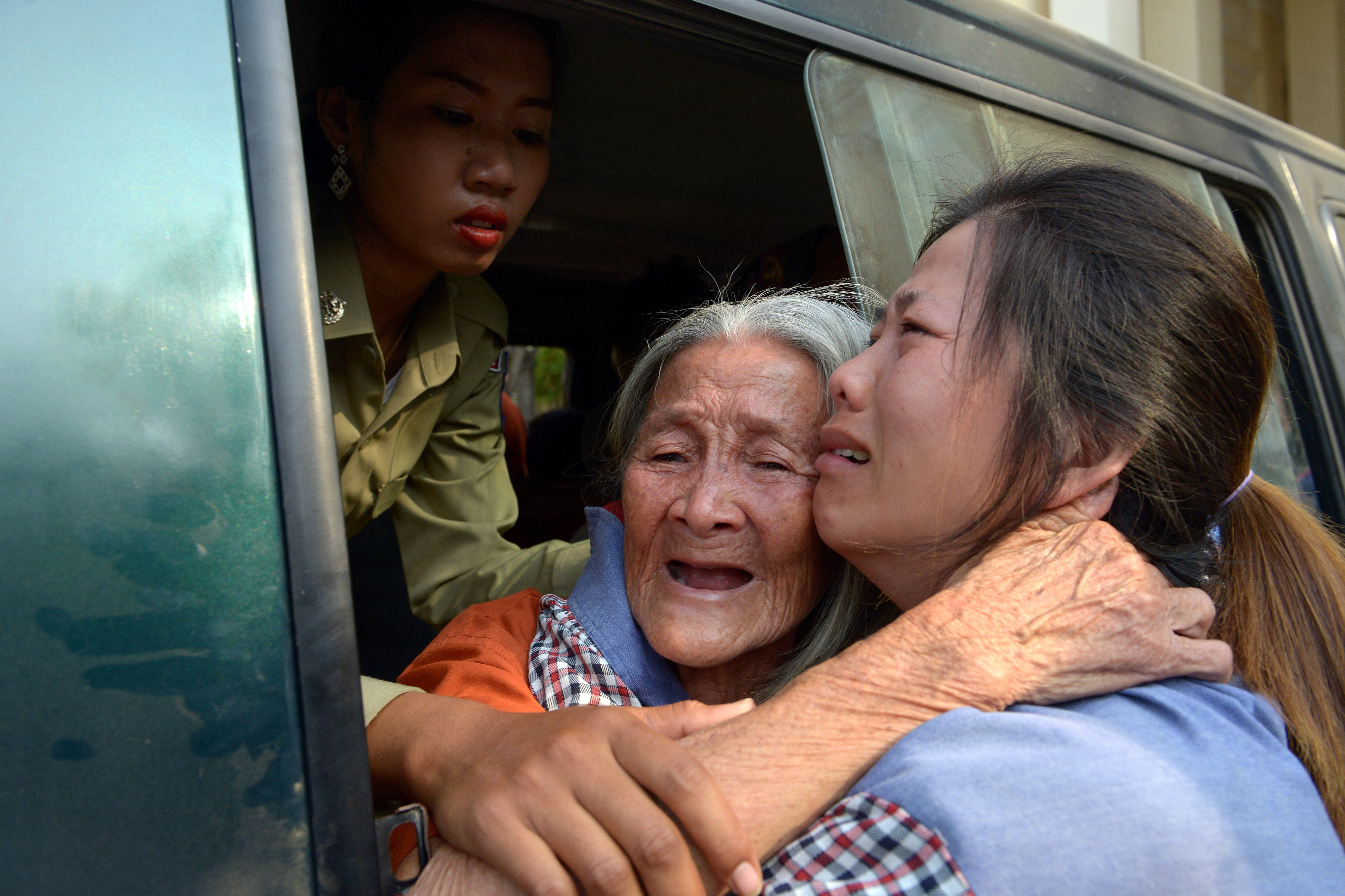 <p>Cambodian land rights activist Nget Khun hugs her daughter through a window of a prison car before a court hearing in Phenom Penh on Jan. 26, 2015. Khun was arrested for protesting against evictions connected to a World Bank-financed land management program.</p>