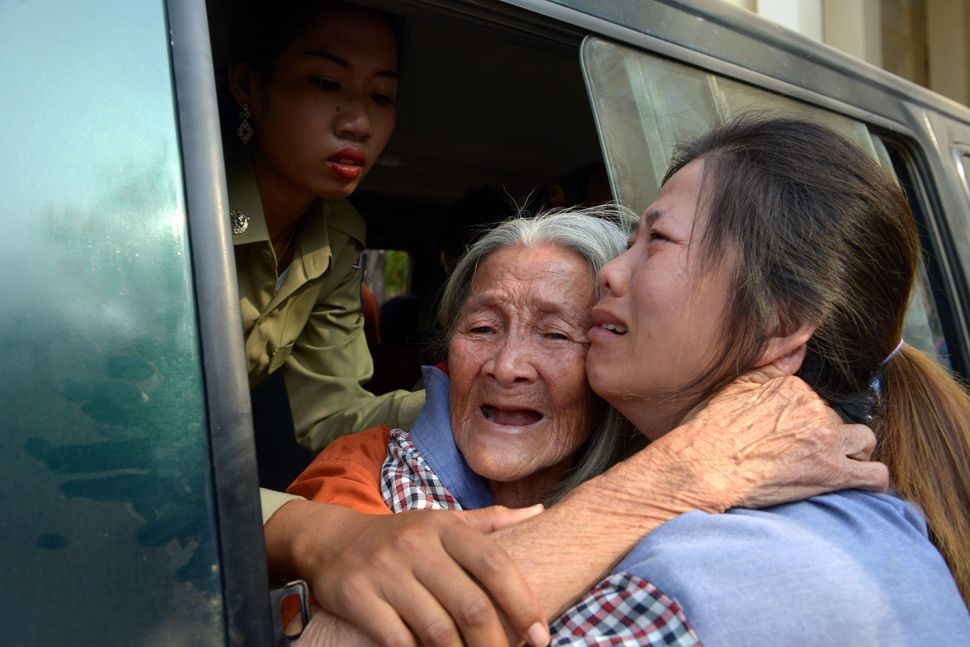 Cambodian land rights activist Nget Khun hugs her daughter through a window of a prison car before a court hearing in Phenom