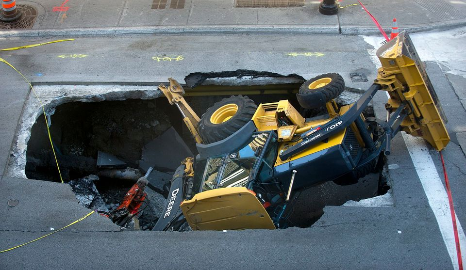 A backhoe is shown on Tuesday, Aug. 6, 2013, after being swallowed by a sinkhole in Montreal . A Montreal business-owner says