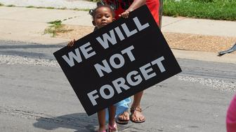 Michael Brown Sr., father of slain 18 year-old Michael Brown Jr., takes stuffed animals to a makeshift memorial prior to a march of solidarity in Canfield Apartments on August 8, 2015 in Ferguson, Missouri. As the embattled community celebrates the one-year anniversary of the shooting of Michael Brown Jr. by a Ferguson police officer, there are a wide range of social events and civil disobedience actions throughout the St. Louis, Missouri area. AFP PHOTO / MICHAEL B. THOMAS        (Photo credit should read Michael B. Thomas/AFP/Getty Images)