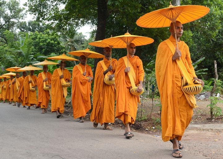<span>Sri Lankan Buddhist monks walk in line as they seek offerings of food in Colombo on July 25, 2015.&nbsp;</span>