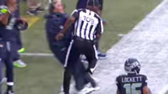 Pete Carroll collides with referee during preseason game.