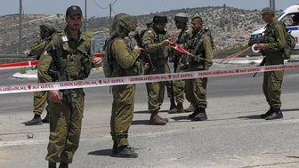 Israeli security forces stand in a security perimeter at the site where a Palestinian young man was shot and wounded by Israeli troops after he had stabbed a soldier on August 15, 2015 near the 'Bel' crossing on highway 443 near the West Bank village of Beit Ur, west of Ramallah. The military said both the soldier and suspected assailant, who was arrested, were lightly wounded.     AFP PHOTO / AHMAD GHARABLI        (Photo credit should read AHMAD GHARABLI/AFP/Getty Images)