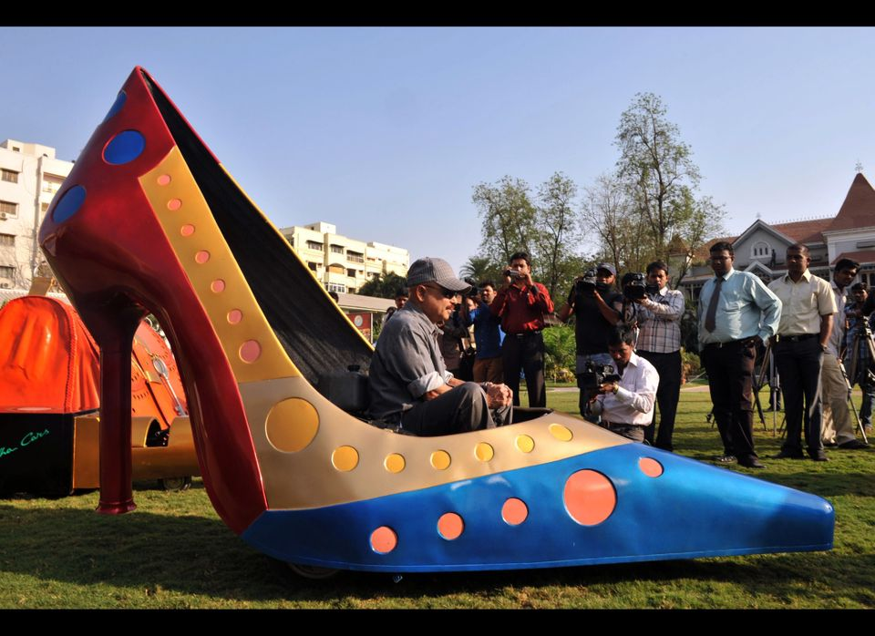 Indian wacky car designer Sudhakar Yadav sits inside a vehicle made in the shape of a stilletto shoe in Hyderabad on March, 7