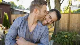 Homosexual couple hugging and kissing in backyard