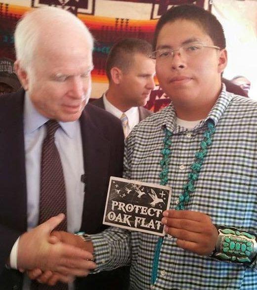 Navajo teen Adriano Tsinigine shakes the hand of Sen. John McCain while holding a small card protesting the sale of Native&nb