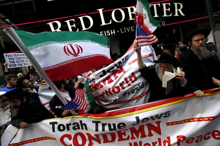 <span>A group of Orthodox Jewish counterdemonstrators wave American and Iranian flags as they stand amid protesters who were