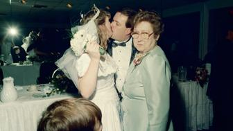 Bride and groom kissing, mature woman looking away