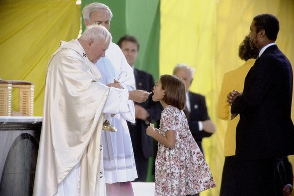 Young girl receives communion from Pope John Paul II as they celebrate Mass at Aqeduct Race Track in Jamaica, Queens, on Oct.