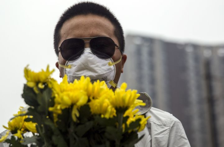 A resident holds flowers at a vigil for the victims of the explosions at a chemical warehouse in Tianjin on Aug. 18, 2015.&nb