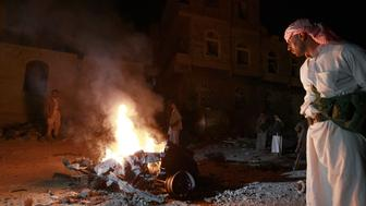 <p>Yemenis look at the wreckage of a vehicle at the site of a car bomb attack in the capital Sanaa on Aug. 13, 2015.</p>
