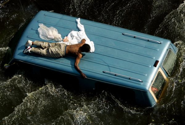 A man clings to the top of a vehicle before being rescued by the U.S. Coast Guard from the flooded streets of New Orleans in
