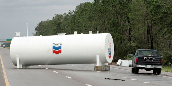 A truck maneuvers around a large fuel tank, carried by floodwaters onto Interstate 10 near Gulfport, Mississippi, on Aug. 29,