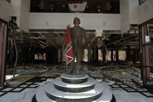 A statue of Jefferson Davis is seen with a Confederate flag that came to rest in the statue's hand, having been blown th