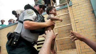 NEW ORLEANS - AUGUST 30: Mark Benton, of Louisiana Department of Wildlife and Fisheries, helps to rescue three month old Ishmael Sullivan from a school rooftop after he and his mother were trapped with dozens of others in high water after Hurricane Katrina August 30, 2005 in New Orleans, Louisiana. Katrina made landfall as a Category 4 storm with sustained winds in excess of 135 mph.  (Photo by Mario Tama/Getty Images)