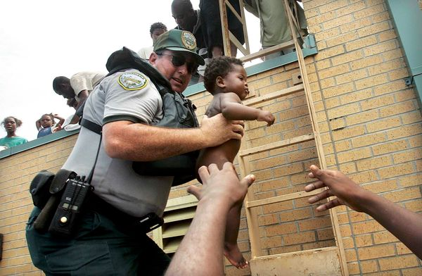 Mark Benton, of the Louisiana Department of Wildlife and Fisheries, helps to rescue 3-month-old Ishmael Sullivan from a schoo