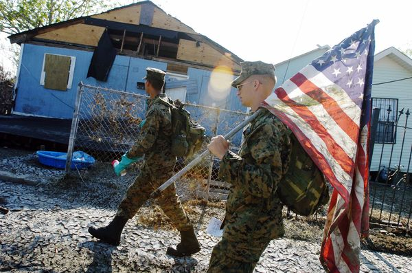 Cpl. Karl Krebsbach carries a tattered and muddied American flag he found as he and other Marines from Camp Lejeune, North Ca