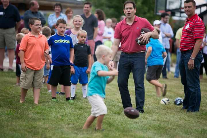 Republican presidential hopeful Sen. Marco Rubio (R-Fla.) reacts as a child fails to catch a football during a Family Night e
