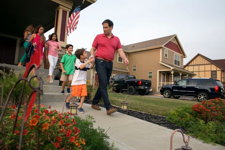 Republican presidential candidate Sen. Marco Rubio (R-Fla.) holds hands with his son, Anthony, as he leaves the porch of