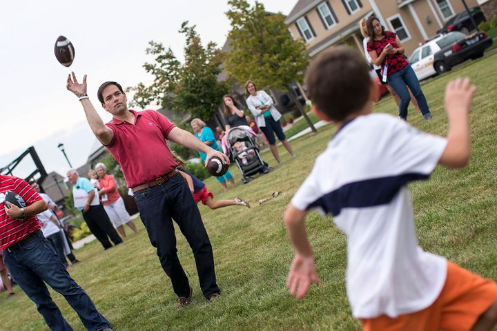 Republican presidential candidate Sen. Marco Rubio (R-Fla.) throws a football with children during a Family Ni